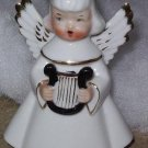 Angel figurine playing harp and singing