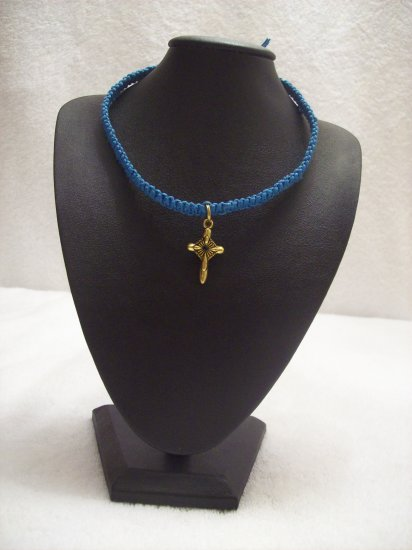 Small gold cross on royal blue square