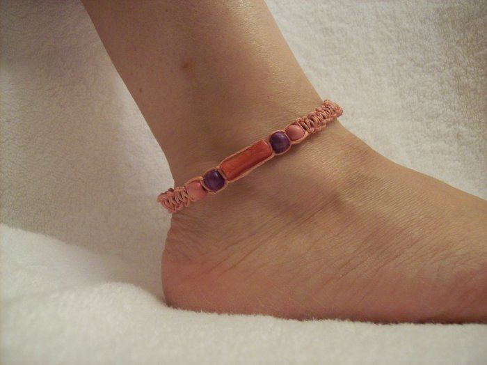 Pink cyllinder with wooden beads on pink square