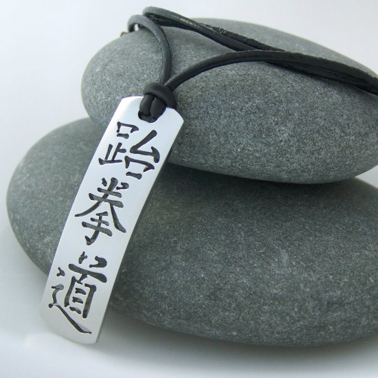 Taekwondo in kanji, stainless steel pendant on natural leather cord. A surfer style necklace