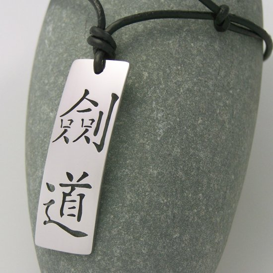 Kendo in kanji, stainless steel pendant on natural leather cord. A surfer style necklace