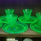 Vaseline Depression Glass snack plates with glasses.