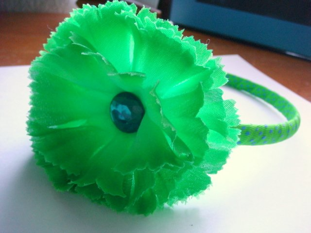 green carnation headband on lime green with blue polka-dots band