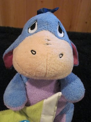 Plush Eeyore holding a blanket with a ladybug on it plush Rattle toy