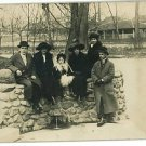 RPPC MEN WOMEN GIRL  IN OVERCOATS SITTING ON STONE WALL