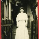 RPPC WOMAN STANDING  GATE HOUSE WAITING AT THE GATE