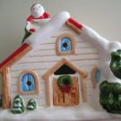CHRISTMAS  HOUSE W/CANDLE & SANTA ON SNOW COVERED ROOF