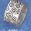 STERLING SILVER HIGH POLISH 11MM BAND WITH ANTIQUED CIRCULAR SCROLL MARKS.