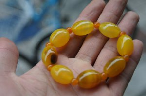 Natural yellow (agate), hand-carved, football-shaped beads (bracelets). Rubber band strung