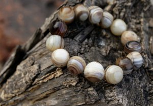 The sardonyx bracelet. 14 mm, 15 beads, irregular pattern. The rubber bands strung.