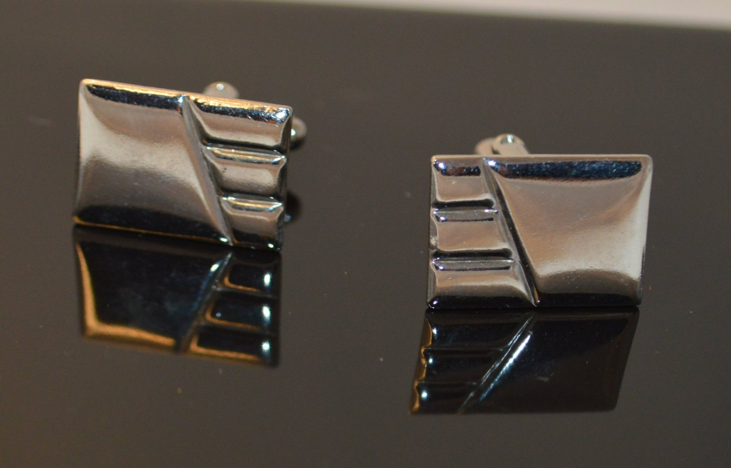Silver toned metal cuff links with 3 sized Ridge Stamped in the metal