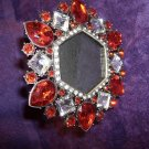 SMALL PICTUE FRAME SURROUNDED BY SIMULATED RUBYS AND CLEAR STONES