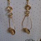 Gold cowry shell hoop style earrings with swirls.