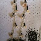 Silver chain style earrings. With puka shell, heart glass beads and black bead accents