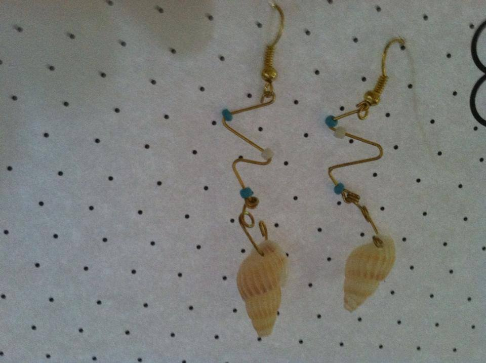 Cone shell earrings with blue and white bead accents.