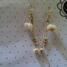 Chandelier style puka shell earrings with reggae bead accents.