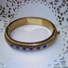Brassy vintage hinged clamper cuff style bangle bracelet with 6 blue rhinestones in goldtone