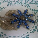 Blue rhinestones brooch pin on silvertone with gold highlights metal flower