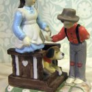 Handpainted bisque figure of boy bringing flowers to girl on porch with dog