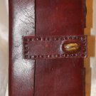 Handmade leather journal with gem stone in front and two gem stones on the edge, with a strap.