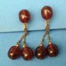 VINTAGE CLIP ON EARRINGS WITH DANGLING AMBER COLORED BEADS ON GOLD TONE CHAINS