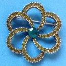 "Green rhinestone flower pin 1 3/4"" in diameter."