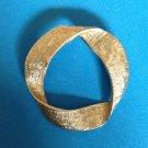 "Pin, gold tone satin & shiny finish, twisted design @ 1 1/2"" diameter."