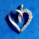 14k white gold pendant. Heart w/ 12 graduated clear stones