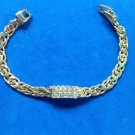 "Chain bracelet, gold tone with 3 rows of clear stones in the center  - 7"" long."