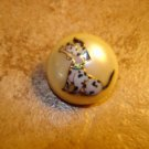Dome shape plastic button with sitting dog.