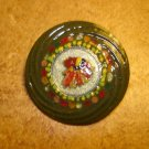 Large colorful metal button with feathers.
