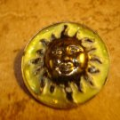 Large metal button with smiling sun.
