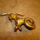 Gold tone metal button in shape of ram goat and rhinestones.
