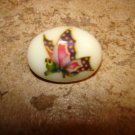 Oval shape ceramic button with colorful butterfly.