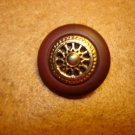 Brown plastic button with gold metal wheel.