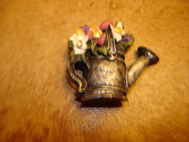 Pewter button in shape of watering can with flowers.