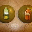 Set of 2 large old celuloid buttons with orange and citrus lemonade.