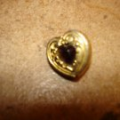 Heart shape gold metal button with garnet color stone.