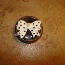 Large gold metal button with large bow.