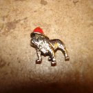 Tiny metal button with buldog dog in red hat.