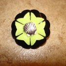 Black carved plastic button with metal sea shell.