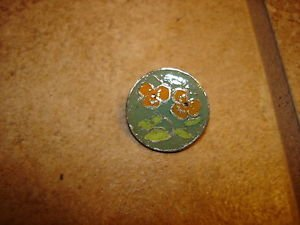 Signed silver metal button with orange flower.