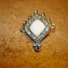 Silver metal button with pearl and blue rhinestones.