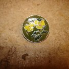 Signed silver metal button with yellow flower.