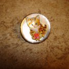 Mother of pearl button with orange cat holding a fish.