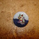 Nicely painted button with sailboat.