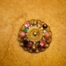 Antique brass button with colorful rhinestones.