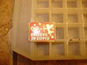 "Gold metal  pinback pins ""I believe in Cupid""."