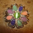 Large silver metal button in shape of flower with jade color stone.