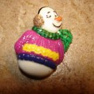 Lovely snowman button with colorful sweater and scarf.